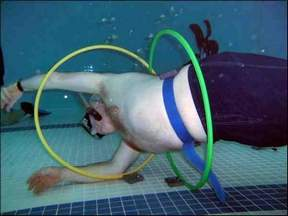 Man swims through suspended hula hoops