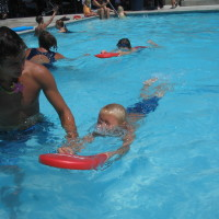 Swimmer with Instructor holding kickboard